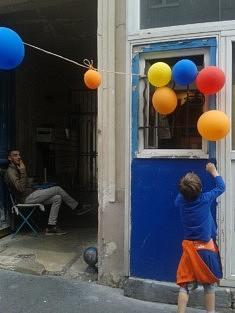 """""""L'enfant aux ballons"""" sur cette photo prise aux Portes Ouvertes en mai 2018, on dirait le même petit garçon avec les cages à oiseaux ! Pourtant, 6 ans séparent ces deux photos : """"l'enfant aux oiseaux"""" a été prise à Rome en 2012 aux premiers beaux jours et ce cliché date de mai 2018. Qu'il cherche à attraper un des ballons devant ma studette ou qu'il cherche à libérer les oiseaux, il s'agit bien du même élan commun car les cages n'abritent plus d'oiseaux mais le concept d'atteindre l'objectif est plus fort que tout et devient un rêve accessible à portée d'un bout de bois. L'enfant ne change pas, il est comme une réprésentation, une répétition miraculeuse qui ne vieillit pas. Sur mes deux photos, ces petits bonhommes se sont invités devant mon objectif, je ne les connais pas et pourtant ils me paraissent familiers puisqu'ils se ressemblent tellement. Ils cherchent à grandir, l'imaginaire grand ouvert mais j'ai saisi leur âme d'enfant au même âge."""