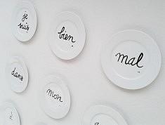 """LE """"JE"""" DES 9 ASSIETTES Sur votre table, vous pourrez disposer ces 9 petites assiettes sur lesquelles j'ai dessiné mots et ponctuation. Il s'agit de recomposer la phrase cachée : """"Je suis - bien - mal - dans - mon - assiette - à - Paris - !"""". Cette idée m'est venue pour l'exposition collective des Ateliers d'Artistes de Belleville à Paris en janvier 2016 en hommage aux victimes des attentats du 13 novembre 2015. Pour moi, le claim """"Je suis Paris !"""" était limitatif et n'exprimait pas assez d'émotions. Aussi, j'ai proposé à travers cette phrase de rajouter des mots pour qualifier de vrais sentiments. C'est-à-dire, """"comment"""" je me sens à Paris ? Bien ? Mal ? Soulagement d'être sains et saufs mais aussi nausée pour cette triste loterie… Acte de présence sur terre, élan de solidarité mondiale… Tel a été mon véritable ressenti. En janvier, dans l'urgence, j'avais présenté le concept sur des assiettes en plastique. Aujourd'hui, J'associe la fragilité et la noblesse de la porcelaine à la valeur de nos vies. Les assiettes à fromage ou dessert symbolisent la fin heureuse d'un repas. Mon jeu de mots intègre l'existence du mal en proposant l'idée qu'il pourrait sortir de table… De façon plus ludique, il s'agit aussi de réfléchir sur les notions de hasard et de destin. Qui aura cette assiette ? Pourquoi ? Où ? Jusqu'où ? Où est le bien ? Où est le mal ? Qui a tort ? Qui a raison ? Qui décide ? S'exprimer autour d'une table ronde afin que chacun puisse être entendu et respecté… Choisir le tête-à-tête avec ses mots préférés ou revendiquer """"Je suis Paris !"""". J'ai pris beaucoup de soin à écrire à la main ce jeu. Chaque assiette est unique, signée et numérotée, résiste au lave-vaisselle. Les premières 9 assiettes réalisées ont été exposées à Turin les 17 et 18 septembre 2016 dans le cadre des Portes Ouvertes de l'association artistique ACCA."""